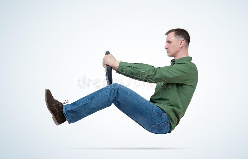 De mens in groene overhemd en jeans drijft een auto met een stuurwiel Autobestuurdersconcept stock foto