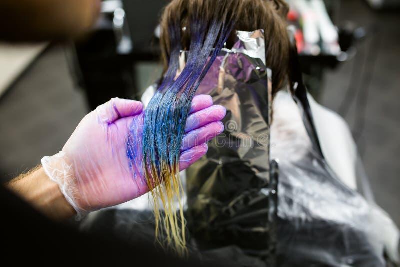 De mens in handschoenen is het sterven lang blauw haar colorfull Schoonheidssalon, Kapper royalty-vrije stock afbeelding