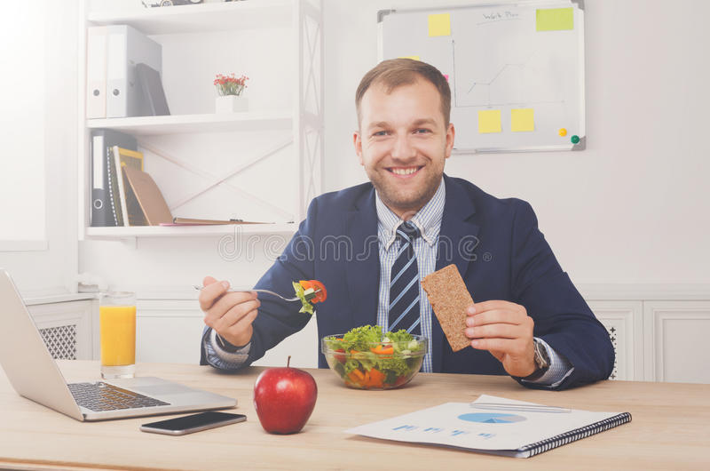 De mens heeft gezonde bedrijfslunch in modern bureaubinnenland stock foto
