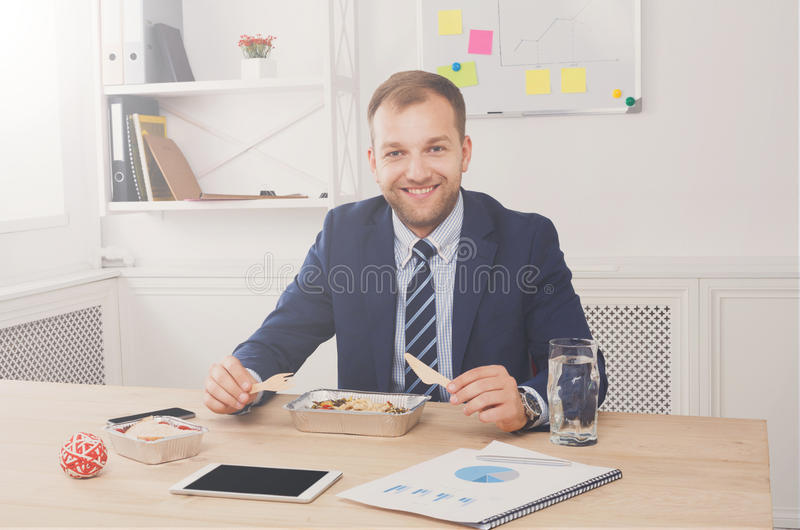 De mens heeft gezonde bedrijfslunch in modern bureaubinnenland royalty-vrije stock afbeelding