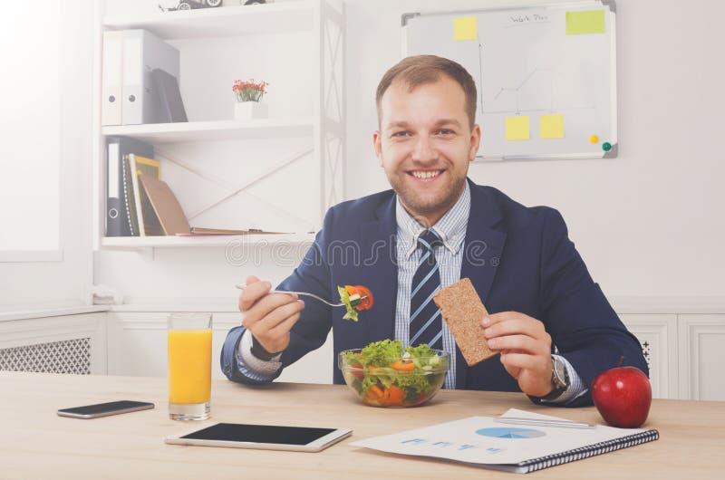 De mens heeft gezonde bedrijfslunch in modern bureaubinnenland royalty-vrije stock afbeeldingen
