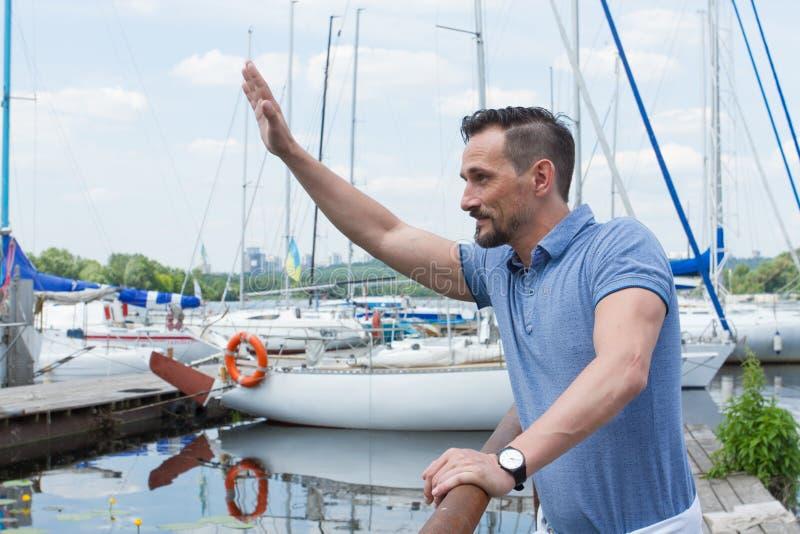 De mens heet met de hand omhoog in rivierjachthaven welkom Jonge zeilers die tot inkomend schip golven Mens dichtbij van pijlerba royalty-vrije stock foto's