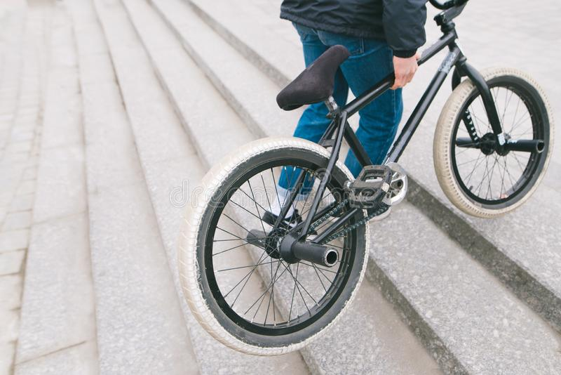 De mens heft de BMX-fiets op de treden tot de bovenkant op Een mens met een BMX-fiets Copyspace stock fotografie