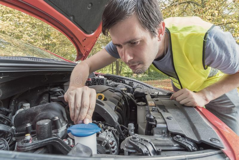 De mens herstelt auto en controleert motorkoelmiddel stock fotografie