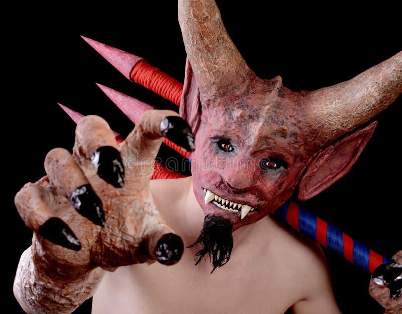 De mens in het masker van de duivel dreigt met zijn hand stock afbeelding