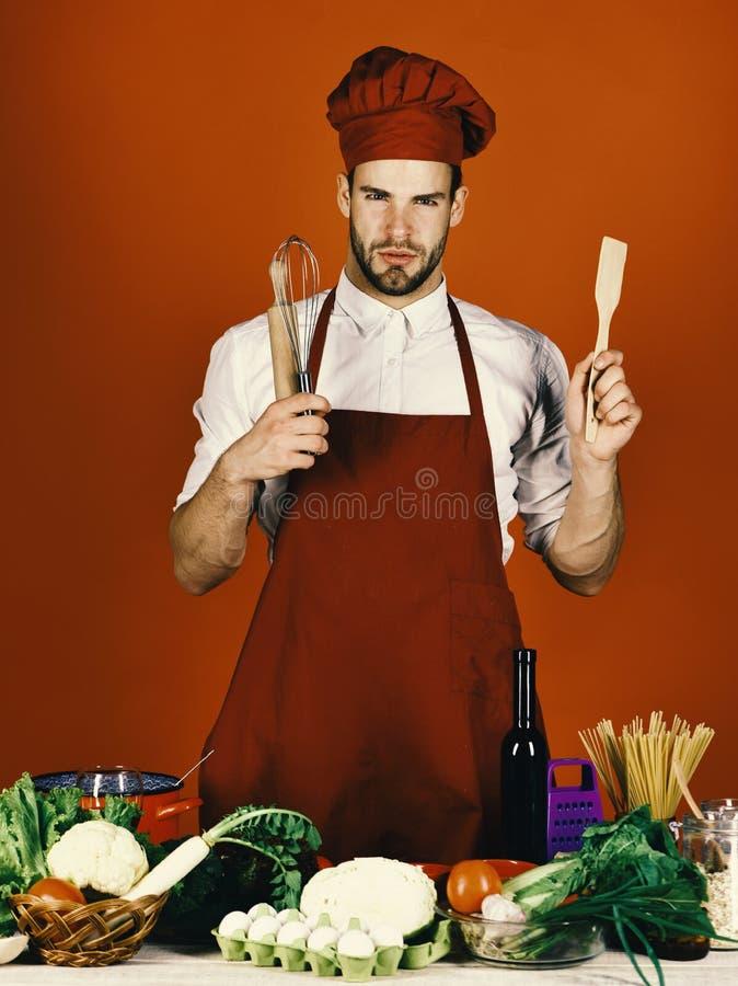 De mens in hoed en schort wordt bereid te koken De mens in hoed en schort wordt bereid te koken Keuken en het koken concept kok royalty-vrije stock foto