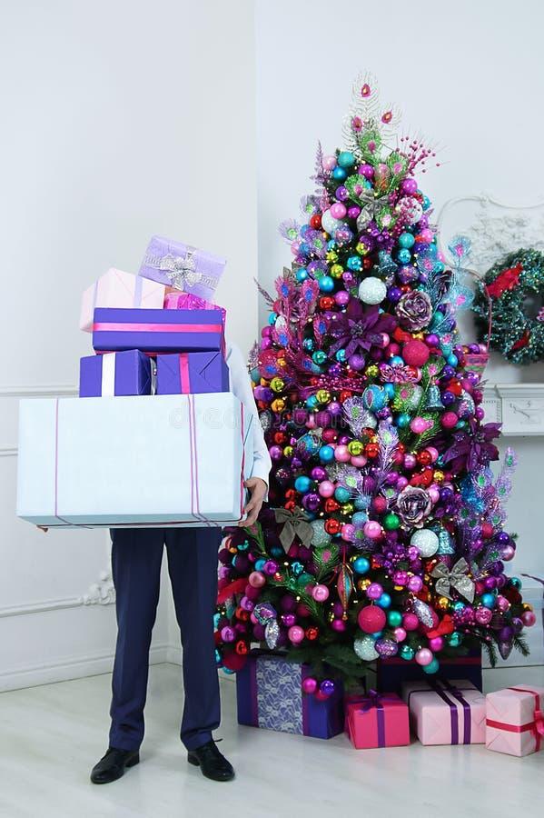 De mens houdt dozen met giften Status naast de Kerstboom stock foto's