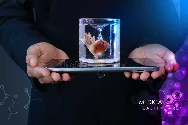 De mens houdt een hart in glas van water en tabletcomputer stock foto's