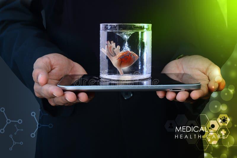 De mens houdt een hart in glas van water en tabletcomputer royalty-vrije stock foto