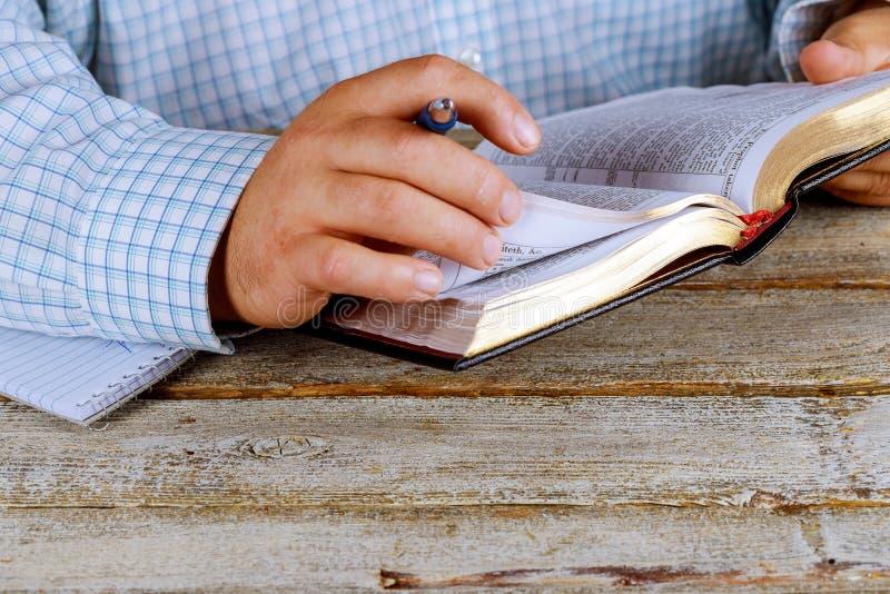 De mens houdt een pen in zijn hand met een open Heilige Bijbel liggend voor hem royalty-vrije stock afbeelding