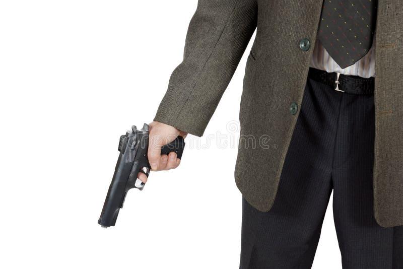 De mens houdt een pistool in zijn hand stock foto's