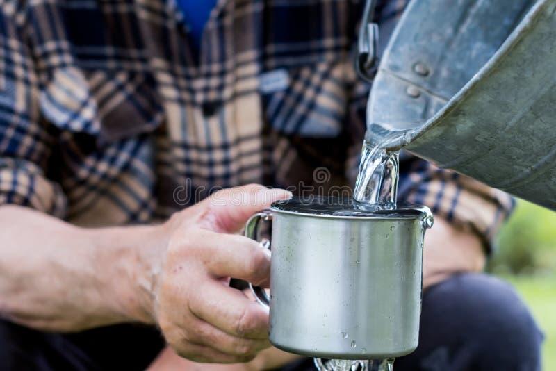 De mens houdt een staalmok en een bronwater giet van een emmer royalty-vrije stock foto's