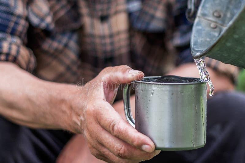 De mens houdt een staalmok en een bronwater giet van een emmer royalty-vrije stock fotografie