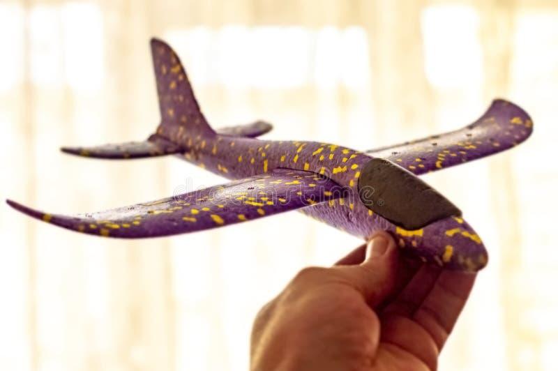 De mens houdt een vliegtuig en de dromen van kinderen plastic van het worden een loods Concept stock foto