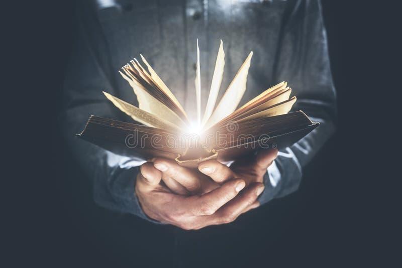 De mens houdt en leest de Heilige Bijbel of een boek stock afbeeldingen