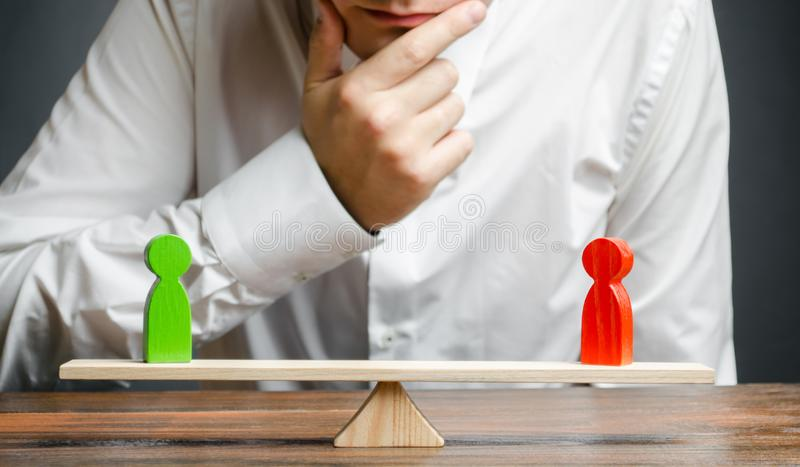 De mens houdt de hand op kin de rivaliserende rode en groene cijfers aangaande schalen bekijkt Gewogen besluit Het concept confli royalty-vrije stock foto