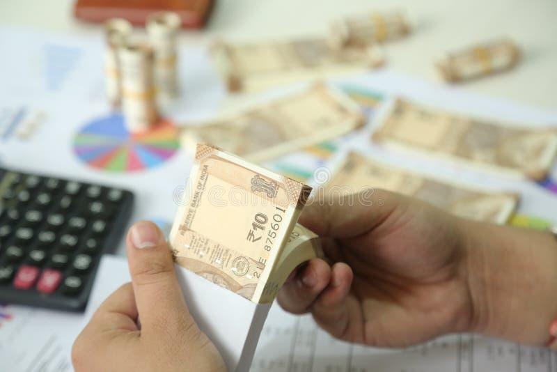 De mens houdt pak Indische in hand nota's van de 10 Roepiesmunt stock fotografie