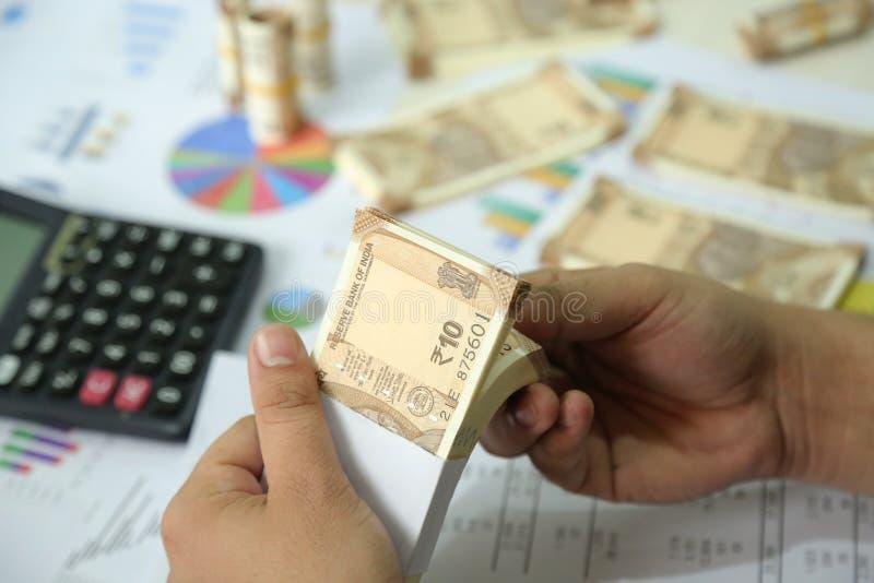 De mens houdt pak Indische in hand nota's van de 10 Roepiesmunt stock foto's
