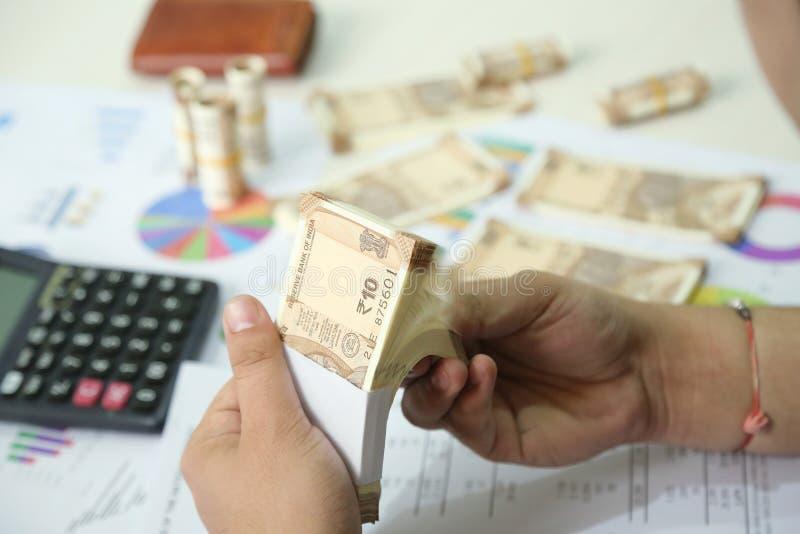 De mens houdt pak Indische in hand nota's van de 10 Roepiesmunt royalty-vrije stock afbeeldingen