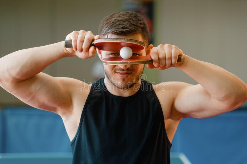 De mens houdt rackets en pingpongbal bij zijn gezicht stock fotografie