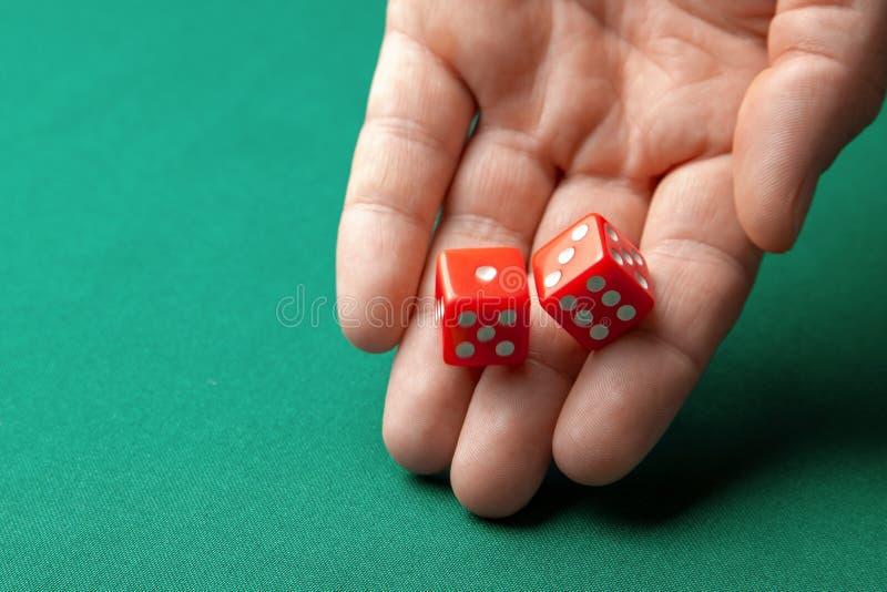 De mens houdt rood twee dobbelt en hen op groene pookspeeltafel in casino werpt Concept online het gokken, winnaar of speler stock afbeelding