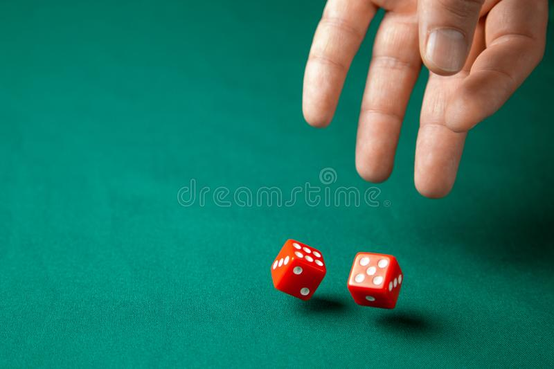 De mens houdt rood twee dobbelt en hen op groene pookspeeltafel in casino werpt Concept online het gokken, winnaar of speler royalty-vrije stock foto's