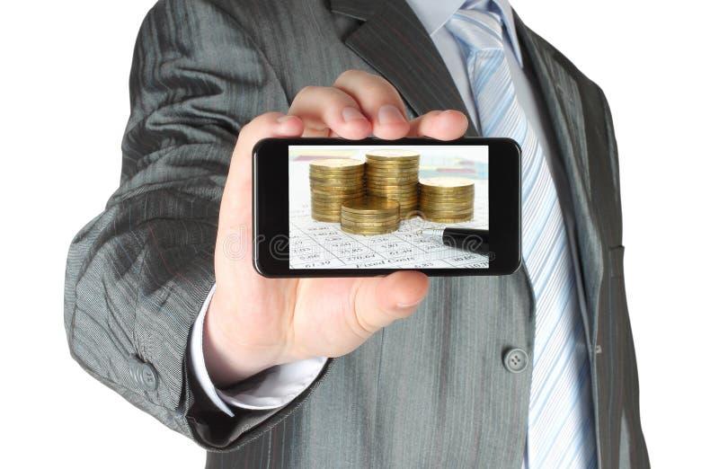 De mens houdt slimme telefoon met bedrijfssamenstelling van grafieken en geld royalty-vrije stock afbeelding