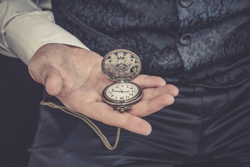 De mens houdt zakhorloge in zijn hand stock afbeelding