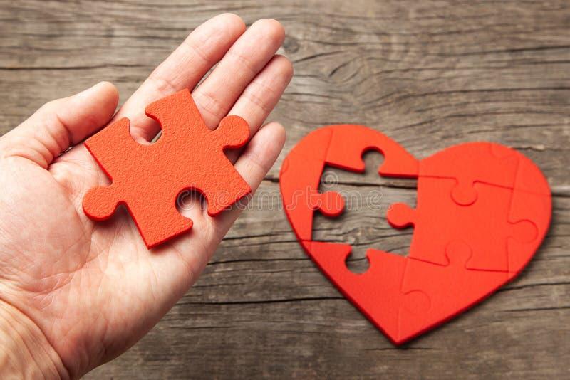 De mens houdt in zijn handdeel van het raadsel van het hart Hoe te om uw boezemvriend of werk voor de ziel te vinden royalty-vrije stock afbeeldingen