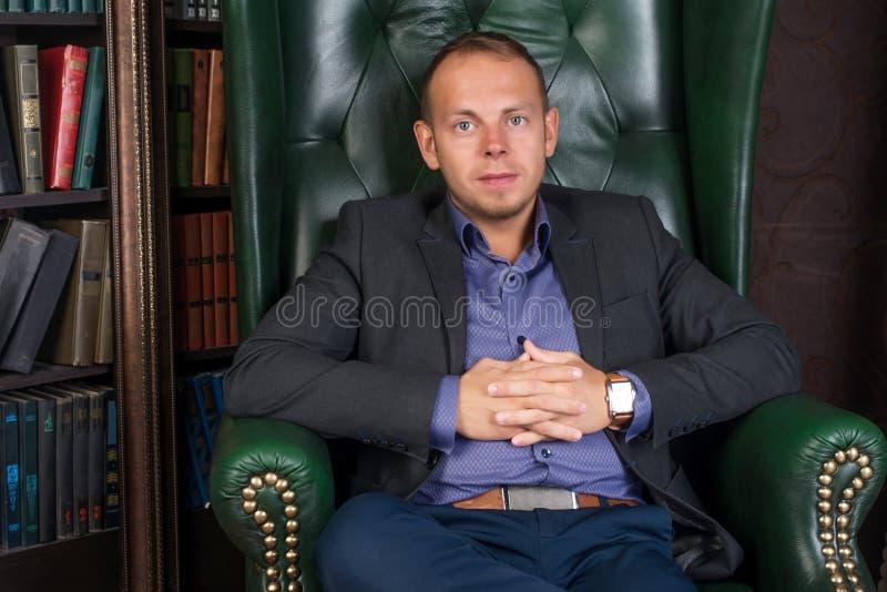 De mens, kalme en zekere zakenmanzitting als voorzitter, bibliotheek royalty-vrije stock fotografie