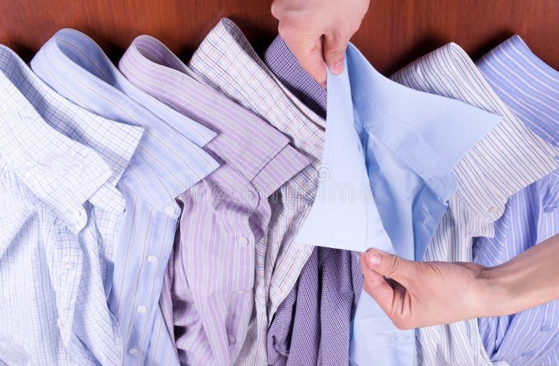 De mens kiest een overhemd stock fotografie