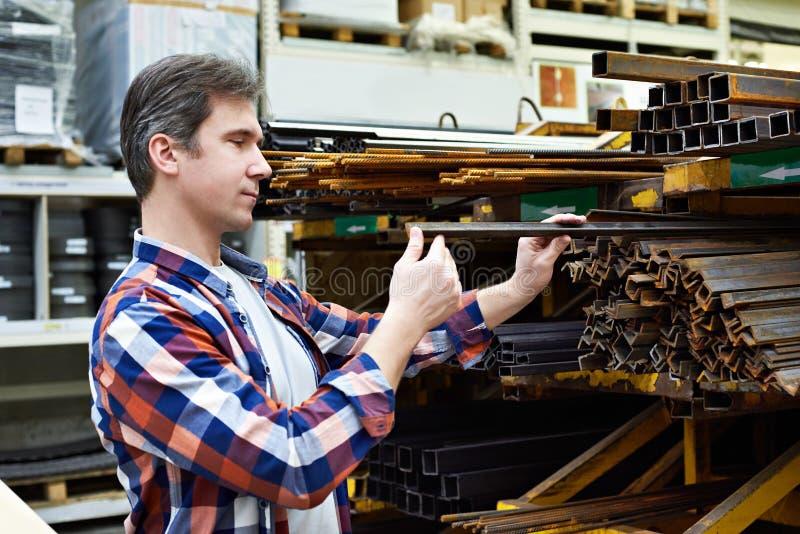 De mens kiest hoek en rebar structureel staal in opslag stock foto