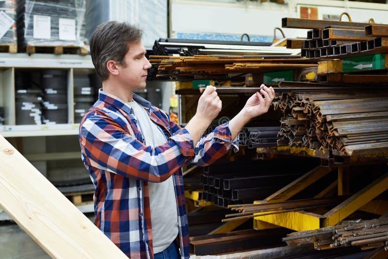 De mens kiest hoek en rebar structureel staal in opslag stock afbeeldingen