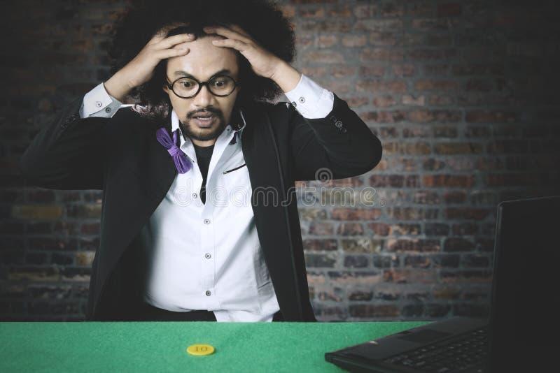 De mens kijkt gefrustreerd na verliest in online pook stock afbeeldingen