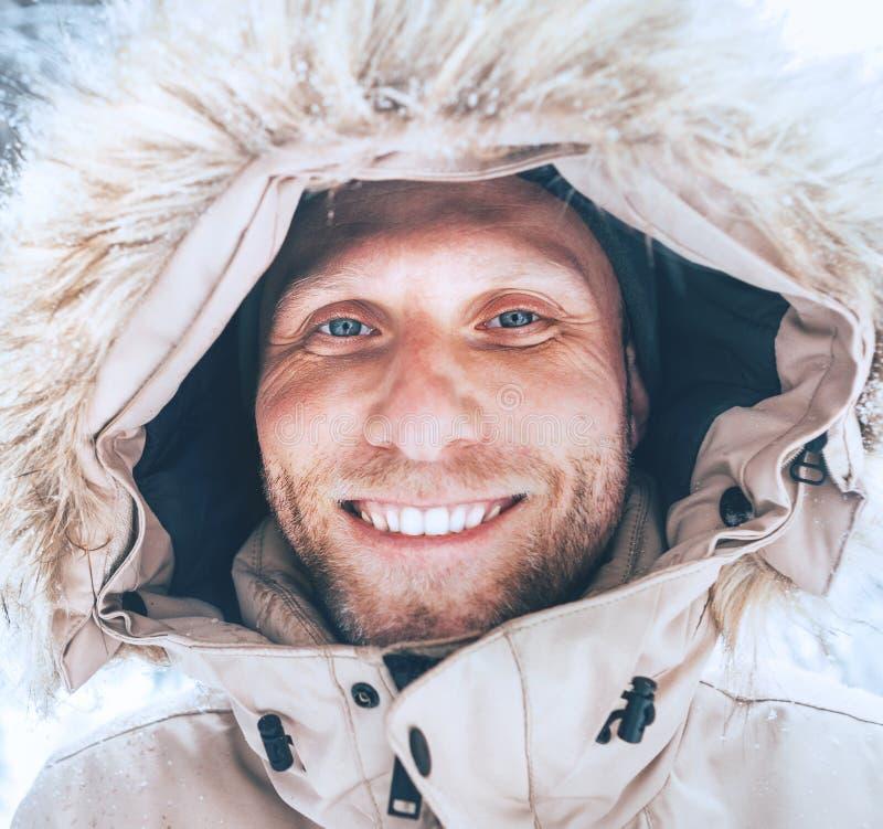 De mens kleedde zich in de Warme Toevallige Bovenkleding Met een kap van het Parkajasje lopend in sneeuw bos vrolijk het glimlach stock afbeelding