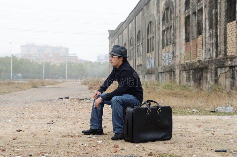 De mens kleedde zich in zwarte met hoedenzitting het roken stock foto
