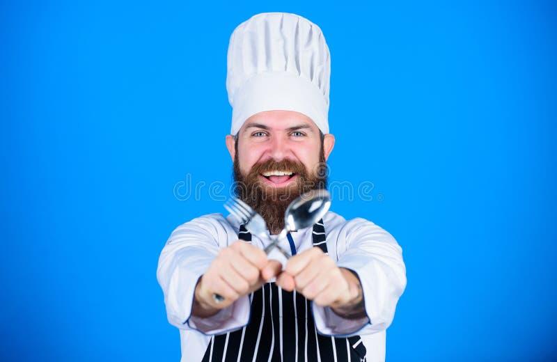 De mens knap met baard houdt keukengerei op blauwe achtergrond Het koken procédé concept Laat pogingsschotel Hongerige klaar chef royalty-vrije stock afbeelding
