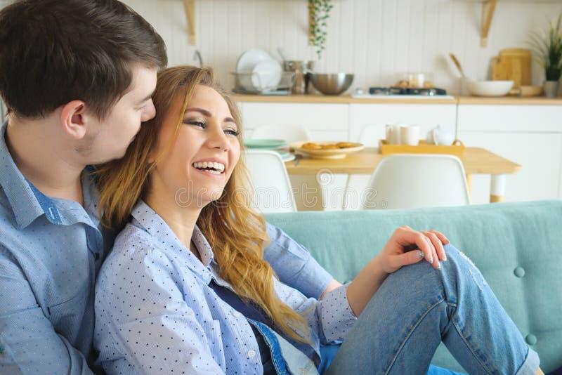 De mens koestert damezitting op bank en het kussen in keuken royalty-vrije stock foto's