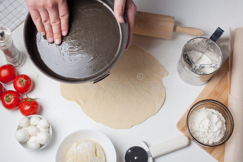 De mens-kok spreidt olijfolie op de pizzavorm uit Op een witte lijst zijn tomaten, mozarellaballen, olijfolie en bloem stock fotografie