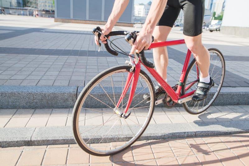 De mens komt neer uit het gordijn op een fiets van de stads rode weg Een fietser die rond de stad cirkelen stock fotografie