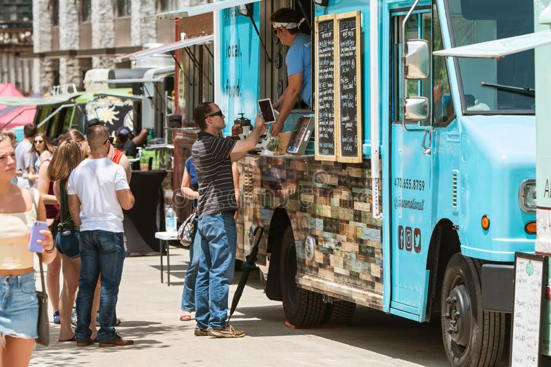 De mens koopt Voedsel in Oud Vierde Ward Food Truck Festival stock foto's
