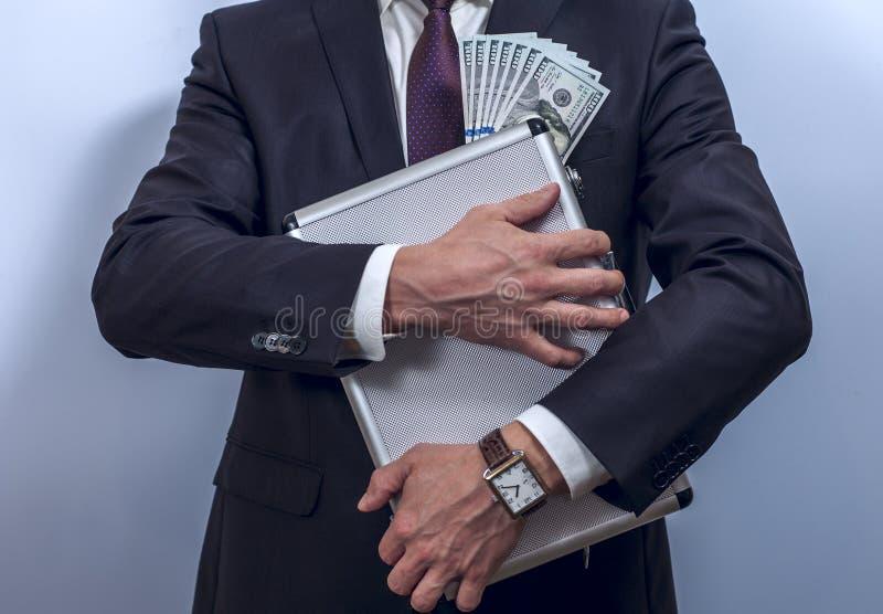 De mens in kostuum houdt metaalaktentas met dollars stock foto's