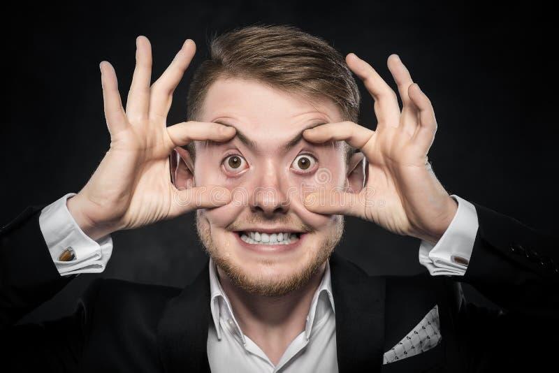 De mens in kostuum maakt grappig gezicht stock afbeeldingen