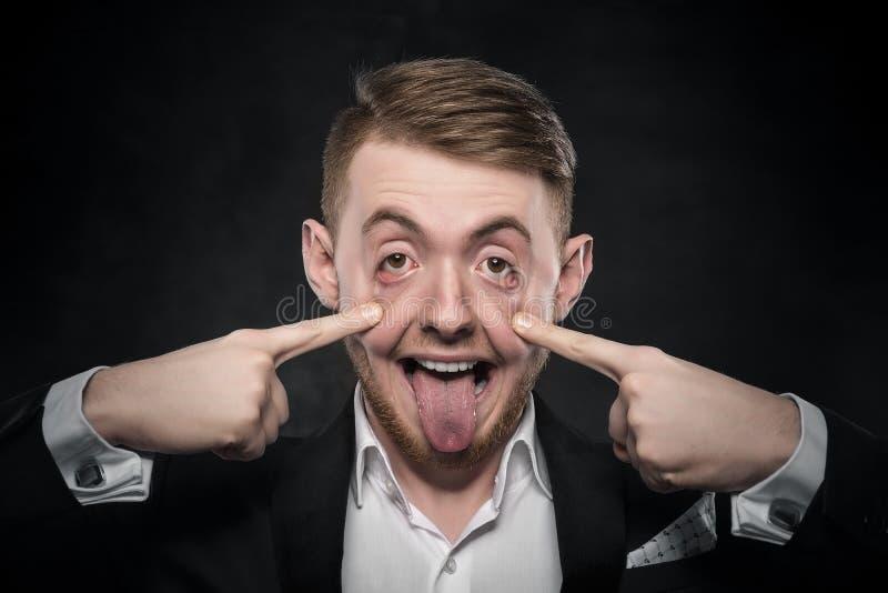De mens in kostuum maakt grappig gezicht royalty-vrije stock foto
