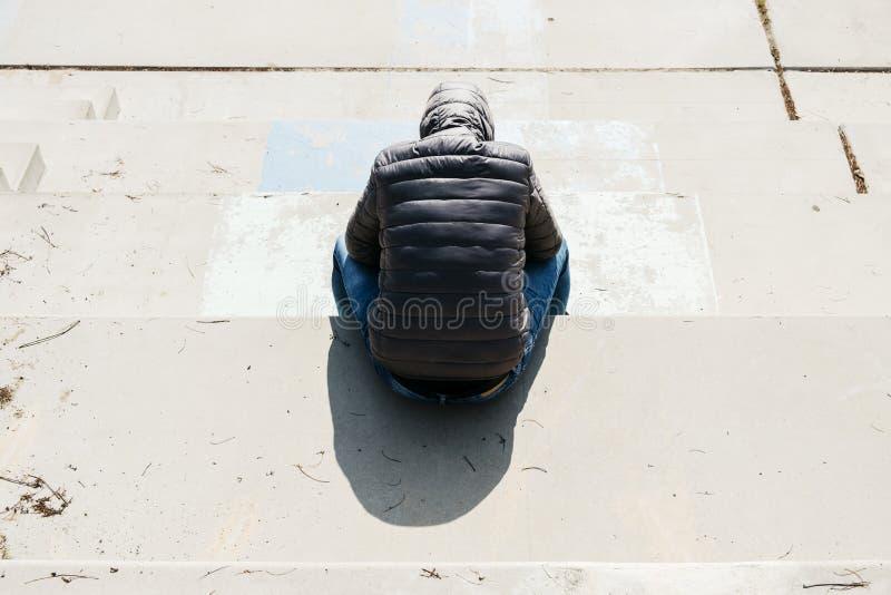 De mens krulde omhoog het zitten op een openluchttrap stock afbeeldingen