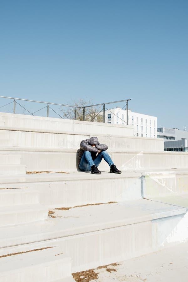 De mens krulde omhoog het zitten op een openluchttrap royalty-vrije stock fotografie