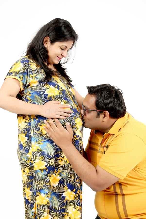 De mens kust de buik van zijn zwangere vrouw royalty-vrije stock afbeeldingen