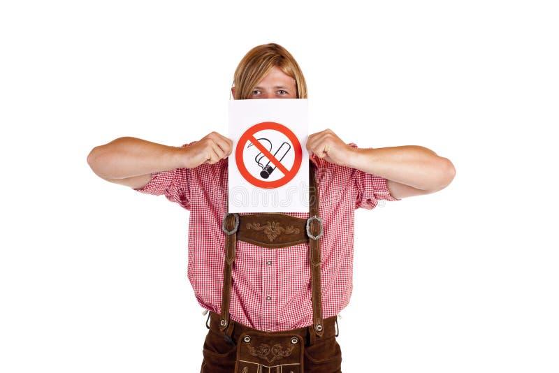 De mens in lederhose houdt geen-smoking-regelteken stock foto