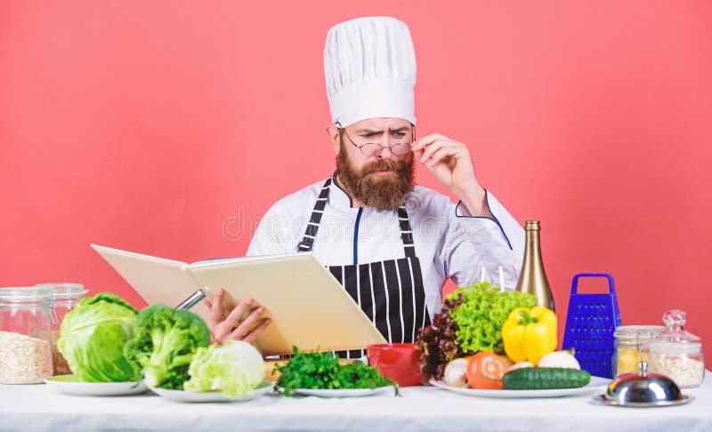 De mens leert recept probeer nieuw iets Het koken op mijn mening Het koken vaardigheid Boekrecepten Volgens recept Gebaarde mens stock afbeelding