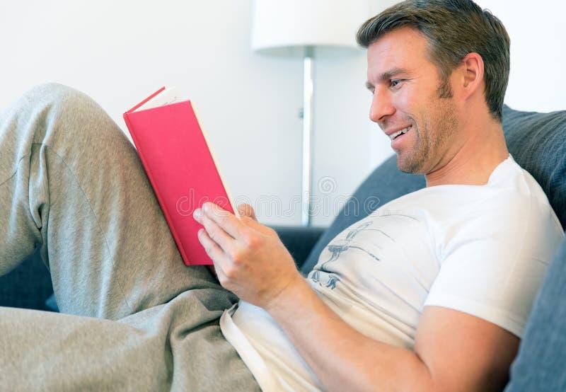 De mens leest een rood boek royalty-vrije stock afbeeldingen